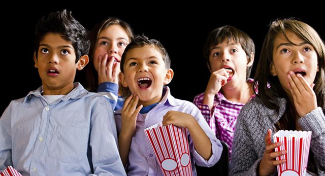 Children eating popcorn and watching a movie
